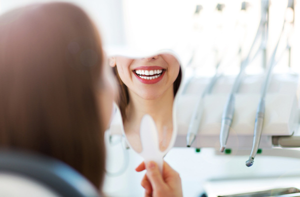 Woman looking at her smile in a mirror at Roane Family Dental in West Linn, OR